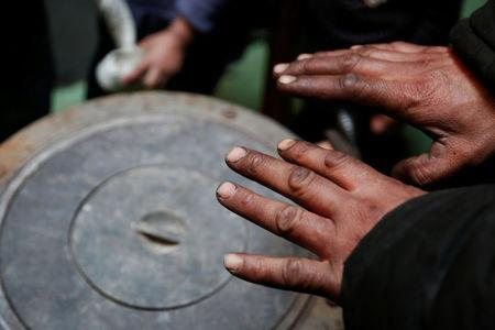 Setevdorj Myagmartsogt holds his hands above his new coal burning stove while talking to reporters in Ulaanbaatar, Mongolia January 29, 2017. Setevdorj Myagmartsogt lives with his wife, four children and two relatives in his cramped ger home above a coal depot not far from the city centre. The government offers free electricity to homes without access to city's central heating grid, but electric heating units are too expensive to families like MyagmartsogtÕs. The family doesnÕt have access to their own electricity line and borrows it from a neighbour. REUTERS/B. Rentsendorj