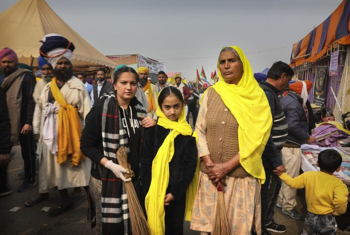 Manjeet Kaur, 60, right, poses for a photograph with her grand daughters as they arrive to give their support during a protest against new farm laws at the Delhi-Haryana state border, on the outskirts of New Delhi, India, Sunday, Dec. 27, 2020. (AP Photo/Manish Swarup)