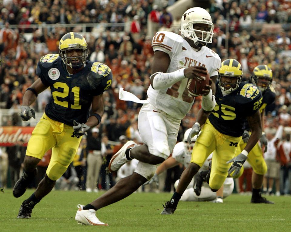 Texas Longhorns quarterback Vince Young (10) sprints 20 yards past Michigan Wolverines free safety Ryan Mundy (L) and safety Ernest Shazor for a touchdown, during the first quarter of the 91st annual Rose Bowl game in Pasadena, California January 1, 2005. REUTERS/Robert Galbraith  RG