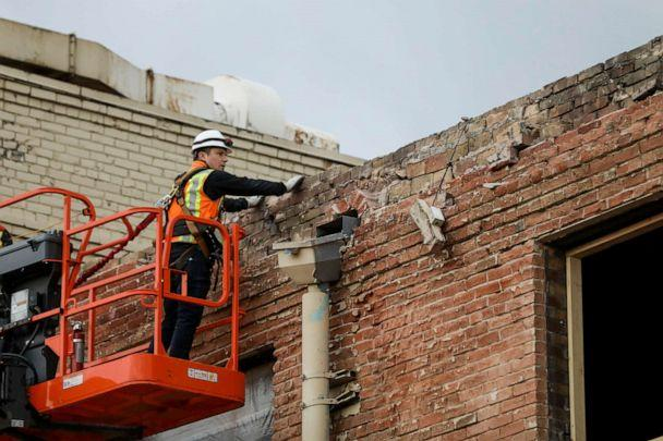 PHOTO: A worker checks the brick facade of a building in Salt Lake City after an earthquake on Wednesday, March 18, 2020. (Spenser Heaps/The Deseret News via AP)