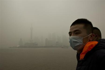 A man wears a face mask while walking on the Bund in front of the financial district of Pudong during a hazy day in downtown Shanghai