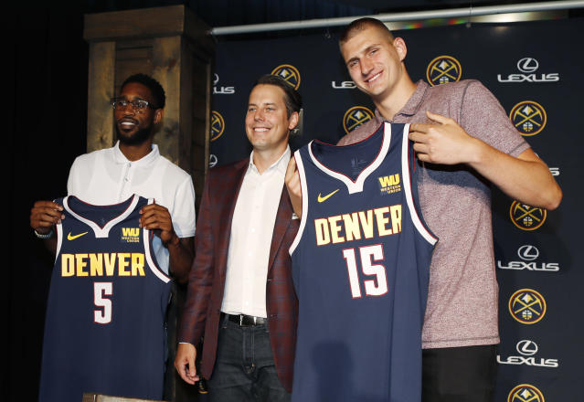 Denver Nuggets center Nikola Jokic, of Serbia, right, joins guard Will Barton, left, and Josh Kroenke, president and governor of the Denver Nuggets, for a photograph during a news conference to outline a contract extension for Jokic and the re-signing of Barton Monday, July 9, 2018, in Denver. (AP Photo/David Zalubowski)