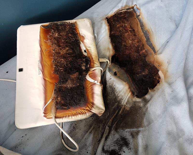Pictured is a burned bed with an imprint of a Samsung tablet. The tablet was charging when it burned through the bed of an 11-year-old boy. It was charging overnight and he woke to a hole in his bed.
