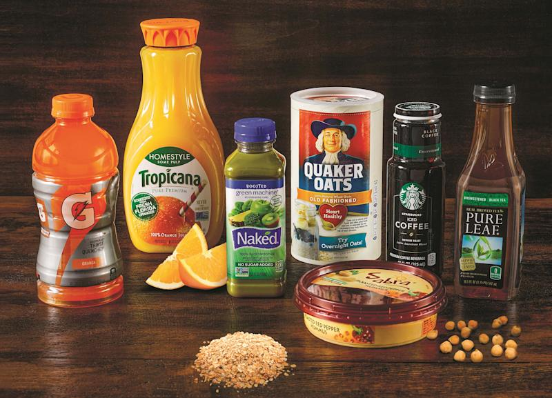 Various PepsiCo products on a wood table, including Gatorade, Tropicana orange juice, Quaker Oats, Sabra hummus, and others.