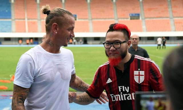 AC Milan fan Liu Shu (R) talks to AC Milan defender Philippe Mexes after a training session ahead of the International Champions Cup match between AC Milan and Inter Milan in Shenzhen on July 24, 2015 (AFP Photo/Johannes Eisele)