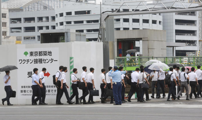 FILE - In this June 16, 2021, file photo, police officers and firefighters arrive to receive the Moderna coronavirus vaccine at a former Tsukiji fish market which was turned to be a temporary mass vaccination center site set up by Tokyo metropolitan government, in Tokyo. After months of delays due to political and bureaucratic bungling as well as a shortage of vaccines, inoculations in Japan are taking off, and the drive is now racing down to the wire with the Olympics starting in one month. (AP Photo/Koji Sasahara, File)