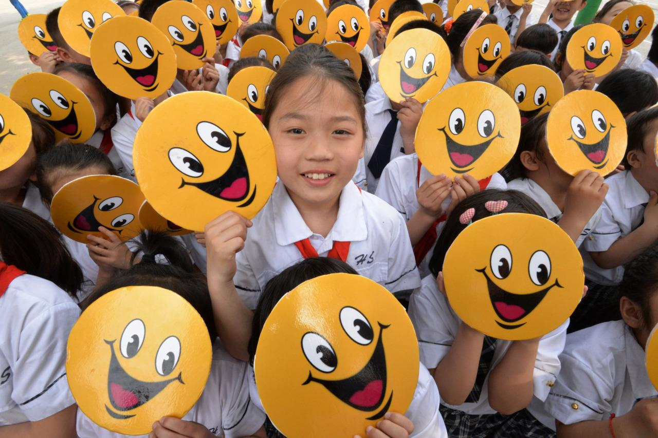 Primary school students in Yongchuan District hold boards of smiling faces to welcome the upcoming World Smile Day on May 5, 2016 in Chongqing, China. (VCG/VCG via Getty Images)