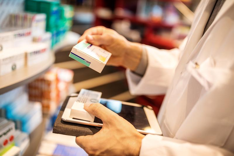 Pharmacist taking stock with digital tablet