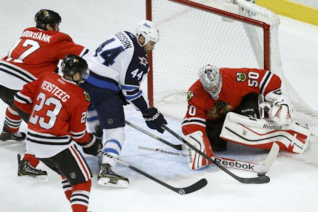Chicago Blackhawks goalie Corey Crawford (50) makes a save on a shot by Winnipeg Jets defenseman Zach Bogosian (44) as Sheldon Brookbank (17) and Kris Versteeg (23) defend during the first period of an NHL hockey game Sunday, Jan. 26, 2014, in Chicago. (AP Photo/Charlie Arbogast)
