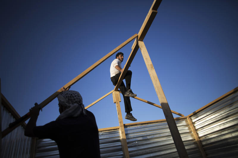 In this Tuesday, Oct. 22, 2013, photo, Syrian refugees build a makeshift house at the Zaatari refugee camp near the Syrian border in Jordan. With Syria's civil war in its third year, more than 2 million Syrians have fled their country. About 100,000 live in this camp. (AP Photo/Manu Brabo)