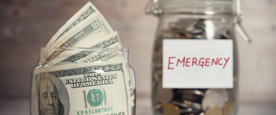 Dollars and coins in glass jar with emergency label.