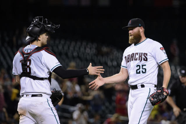 Sep 3, 2019; Phoenix, AZ, USA; Arizona Diamondbacks catcher Carson Kelly (18) and relief pitcher Archie Bradley (25) celebrate after closing out the game against the San Diego Padres at Chase Field. Mandatory Credit: Jennifer Stewart-USA TODAY Sports