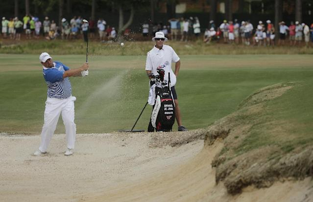 Brendon De Jonge, of Zimbabwe, hits out of the bunker on the seventh hole during the third round of the U.S. Open golf tournament in Pinehurst, N.C., Saturday, June 14, 2014. (AP Photo/Chuck Burton)