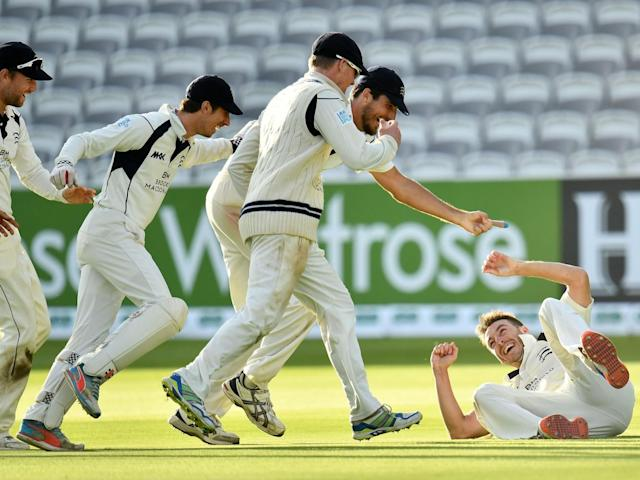 The Middlesex team rush to congratulate Toby Roland-Jones moments after he won the title for his side (Getty)