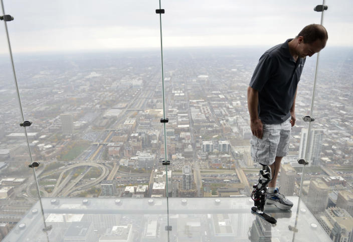 """In this Oct. 25, 2012 photo, Zac Vawter, fitted with an experimental """"bionic"""" leg, looks down from the Ledge at the Willis Tower in Chicago. Vawter is training for the world's tallest stair-climbing event where he'll attempt to climb 103 flights to the top of the Willis Tower using the new prosthesis. (AP Photo/Brian Kersey)"""