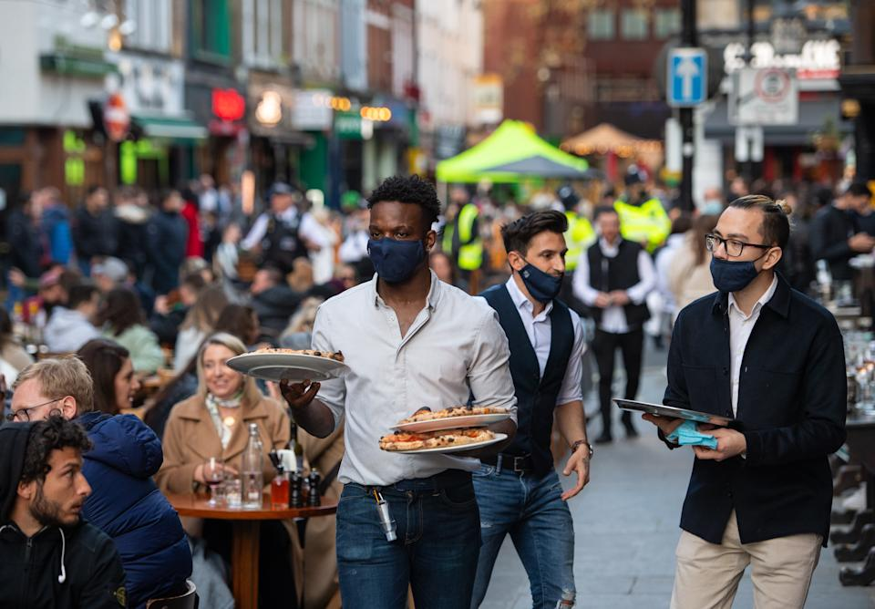 Waiters serve people eating and drinking at outside tables on Saturday evening in Soho, central London, following the further easing of lockdown restrictions in England. Picture date: Saturday April 24, 2021.