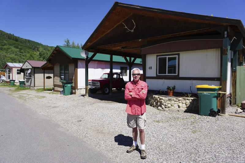 In this July 6, 2019, photo Jeff Morehead stands near his home at the Fish Creek Mobile Home Park in Steamboat Springs, Colo. Some Colorado towns are taking action to preserve their remaining mobile home parks. Cities, counties and housing authorities, such as the Yampa Valley Housing Authority in Steamboat Springs, are buying mobile home parks to preserve affordable housing for residents as other mom-and-pop park owners sell out to developers or investors.(Matt Stensland/The Colorado Sun via AP)