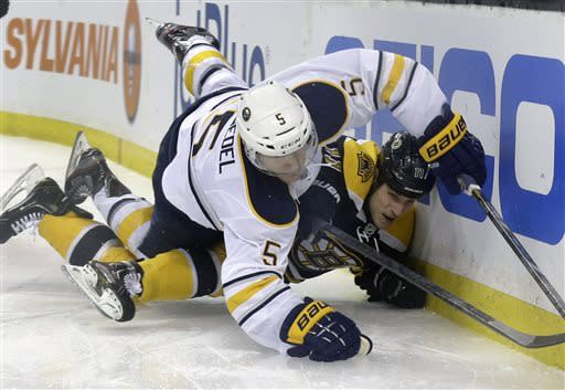 Buffalo Sabres defenseman Chad Ruhwedel (5) falls over Boston Bruins center Gregory Campbell (11) as they battle for the puck along the boards during the second period of an NHL hockey game in Boston, Wednesday, April 17, 2013. (AP Photo/Elise Amendola)