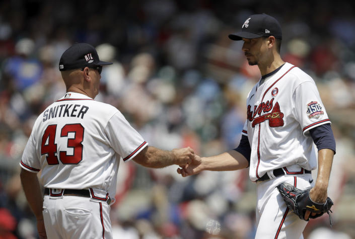 Atlanta Braves pitcher Charlie Morton, right, hands the ball to manager Brian Snitker (43) in the sixth inning of a baseball game against the Miami Marlins, Sunday, July 4, 2021, in Atlanta. (AP Photo/Ben Margot)