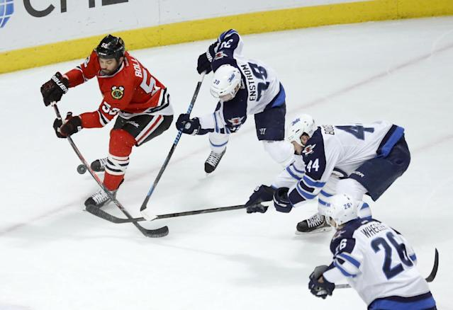 Chicago Blackhawks left wing Brandon Bollig (52) is unable to get a shot-on-goal from the defense of Winnipeg Jets defenseman Tobias Enstrom (39) Zach Bogosian (44) and Blake Wheeler during the first period of an NHL hockey game, Sunday, Jan. 26, 2014, in Chicago. (AP Photo/Charlie Arbogast)