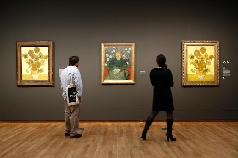 """Visitors look at paintings by Van Gogh, """"Sunflowers"""" and """"La Berceuse (Woman Rocking a Cradle); Augustine Roulin"""" at Van Gogh museum in Amsterdam, Netherlands, Wednesday, May 1, 2013. The Van Gogh Museum has reopened its doors to the public after a seven-month renovation, kicking off with """"Vincent At Work,"""" an exhibition that shows Van Gogh's working methods, right down to the paints, brushes and other tools he used. (AP Photo/Vincent Jannink)"""