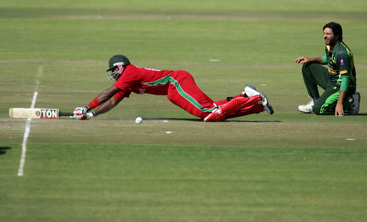 Zimbabwe batsman Hamilton Masakdza survives a run out attempt as Shahid Afridi watches during the first game of the three match ODI cricket series between Pakistan and hosts Zimbabwe at the Harare Sports Club August 27, 2013.AFP PHOTO / JEKESAI NJIKIZANA        (Photo credit should read JEKESAI NJIKIZANA/AFP/Getty Images)