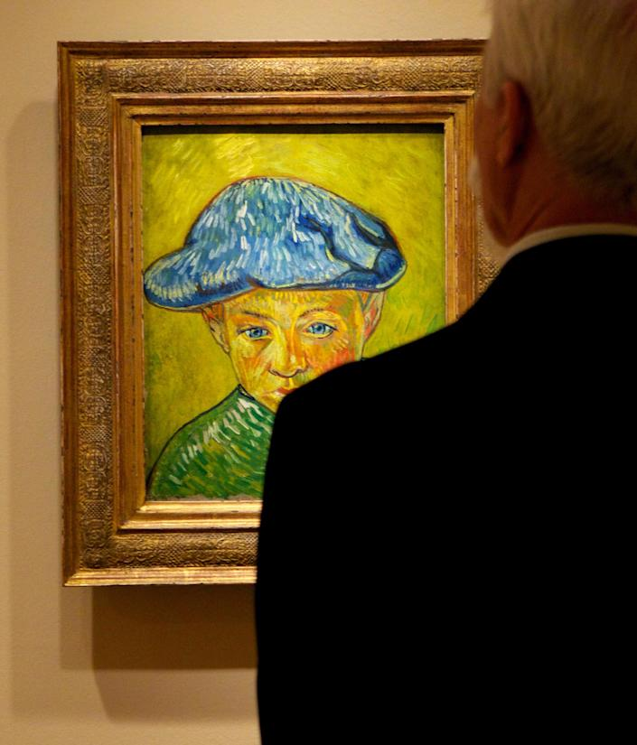 """In this Oct. 8, 2013 photo, a visitor studies Vincent van Gogh's """"Portrait of Camille Roulin,"""" on display at The Phillips Collection in Washington. In the midst of the shutdown of federally funded museums, the private Phillips Collection is launching the first major exhibition of Vincent van Gogh's artwork in Washington in 15 years. (AP Photo/Molly Riley)"""