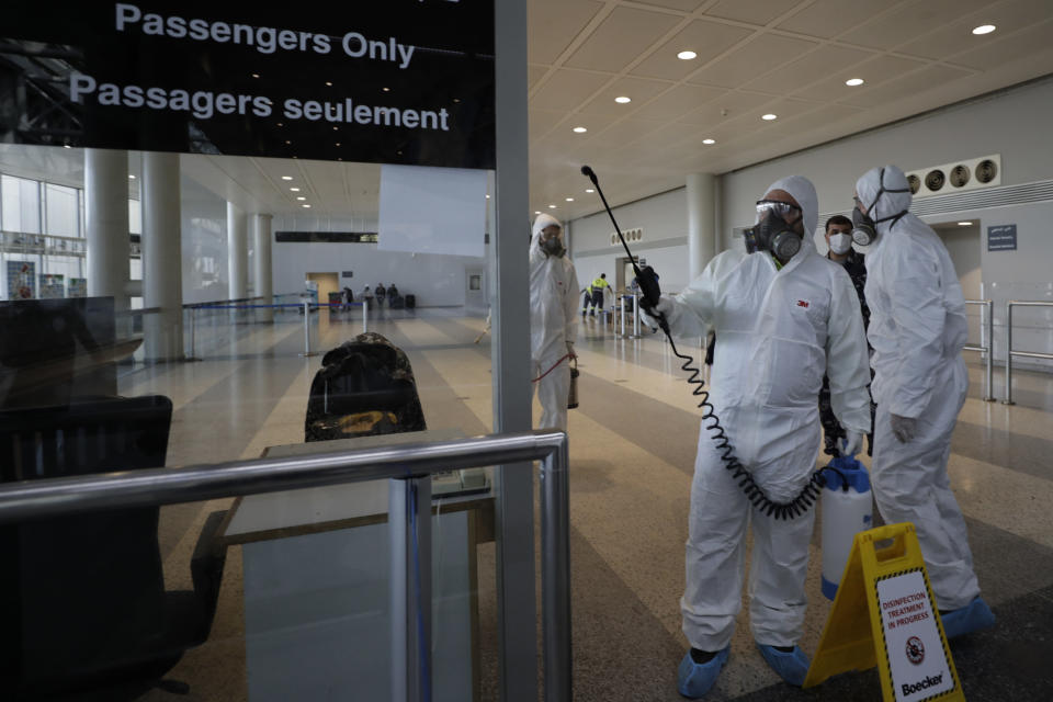 FILE - In this March 5, 2020 file photo, workers wearing protective gear spray disinfectant as a precaution against the coronavirus outbreak, in the departure terminal at the Rafik Hariri International Airport, in Beirut, Lebanon. On Wednesday, July 1, 2020, Beirut's airport is partially reopening after a three-month shutdown and Lebanon's cash-strapped government hopes thousands of Lebanese expatriates will return for the summer, injecting badly needed dollars into the sinking economy. (AP Photo/Hassan Ammar, File)