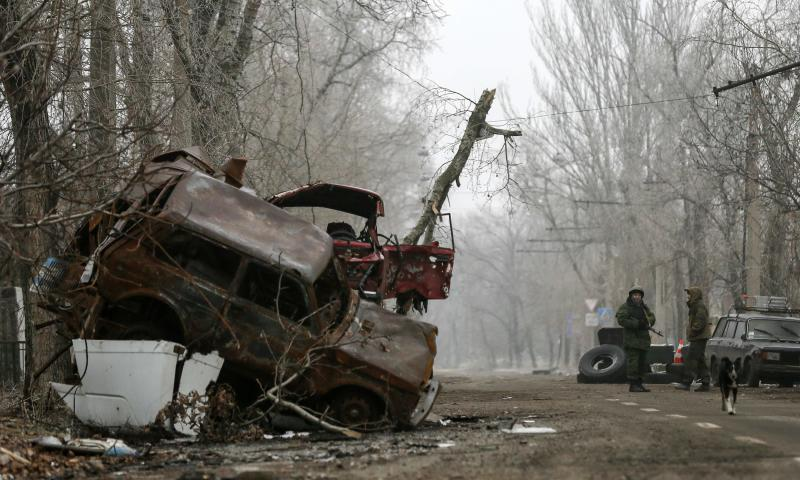 Pro-Russian separatists stand guard next to cars damaged during fighting between pro-Russian rebels and Ukrainian government forces near Donetsk Sergey Prokofiev International Airport, eastern Ukraine, December 16, 2014. REUTERS/Maxim Shemetov (UKRAINE - Tags: POLITICS CIVIL UNREST CONFLICT)