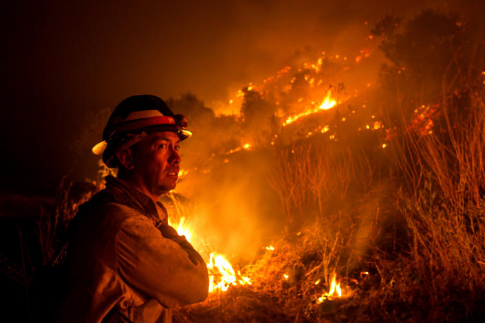 A firefighter watches the Bobcat Fire burning on hillsides in Monrovia, Calif., on Tuesday. (Ringo Chiu/AFP via Getty Images)