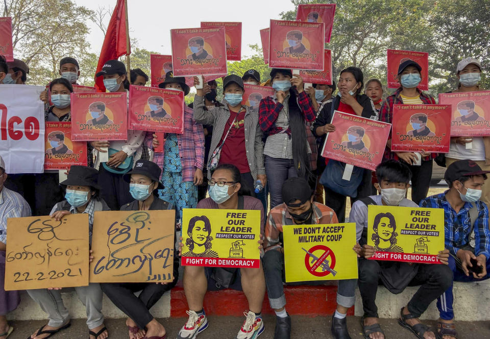 Anti-coup protesters display pictures of deposed Myanmar leader Aung San Suu Kyi and aprotester who was shot and killed by Myanmar security forces during a protest two-days earlier as they gather to protest in Yangon, Myanmar Tuesday, Feb. 23, 2021. Protesters gathered in Myanmar's biggest city despite the ruling junta's threat to use lethal force against people who join a general strike against the military's takeover three weeks ago. (AP Photo)