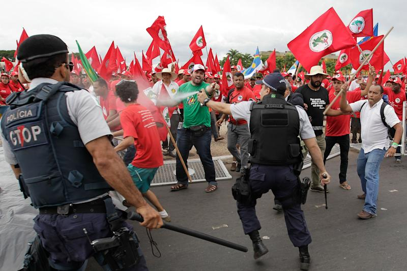 Brazilian riot police clash with demonstrators during a march of The Landless Workers Movement, in front of the Planalto presidential palace, in Brasilia, Brazil, Wednesday, Feb. 12, 2014. The Landless Workers Movement, one of the globe's biggest agrarian reform movements called the protest to demand that the government hand over more unused land to impoverished farmers who have none of their own. (AP Photo/Eraldo Peres)