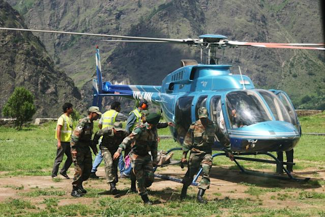 Members of the Indian Army evacuate an injured person during a search and rescue operation in the Chamoli district in the northern Uttarakhand state on June 19, 2013. Military helicopters dropped emergency supplies June 19 to thousands of people stranded by flash floods that tore through towns and temples in northern India and neighbouring Nepal, killing more than 160, officials said. AFP PHOTO