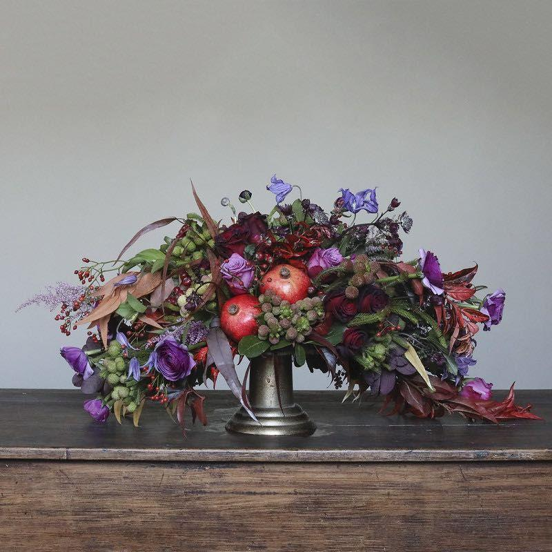"""<p><a href=""""https://mcqueensflowers.com/"""" rel=""""nofollow noopener"""" target=""""_blank"""" data-ylk=""""slk:McQueens New York"""" class=""""link rapid-noclick-resp"""">McQueens New York</a> created a stunning centerpiece suited for your next holiday party. Blooms in deep hues gracefully spill over the vase, making it an ideal shape to fill rectangular tables. The pièce de résistance is the pair of pomegranates unexpectedly nestled within the arrangement.</p><p>If you are local to the New York City area, McQueens will deliver. If you are elsewhere in the United States, you can shop online for seasonal bouquets, or you can work with them directly for custom orders.</p>"""