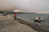 People use a dinghy as a wildfire approaches Limni village on the island of Evia, about 160 kilometers (100 miles) north of Athens, Greece, Friday, Aug. 6, 2021. Thousands of people fled wildfires burning out of control in Greece and Turkey on Friday, including a major blaze just north of the Greek capital of Athens that claimed one life, as a protracted heat wave left forests tinder-dry and flames threatened populated areas and electricity installations. (AP Photo/Thodoris Nikolaou)