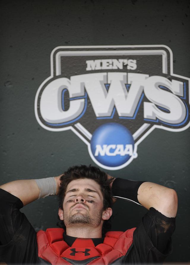 Texas Tech catcher Hunter Redman sits dejected in the dugout following a 2-1 loss to Mississippi in an NCAA baseball College World Series elimination game in Omaha, Neb., Tuesday, June 17, 2014. (AP Photo/Eric Francis)