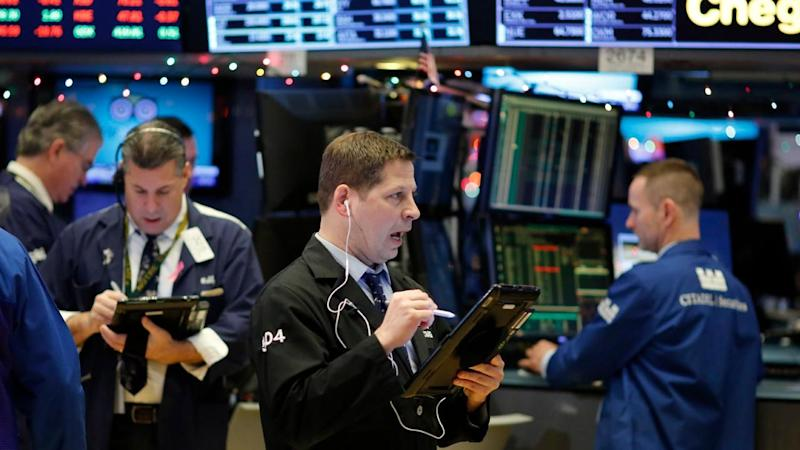 A trio of traders work in a booth on the floor of the New York Stock Exchange Tuesday Jan. 30