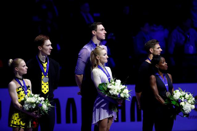 Figure Skating - World Figure Skating Championships - The Mediolanum Forum, Milan, Italy - March 22, 2018 Germany's Aljona Savchenko and Bruno Massot celebrate on the podium after winning the Pairs gold with Russia's Evgenia Tarasova and Vladimir Morozov who won silver and France's Vanessa James and Morgan Cipres who won bronze REUTERS/Alessandro Garofalo