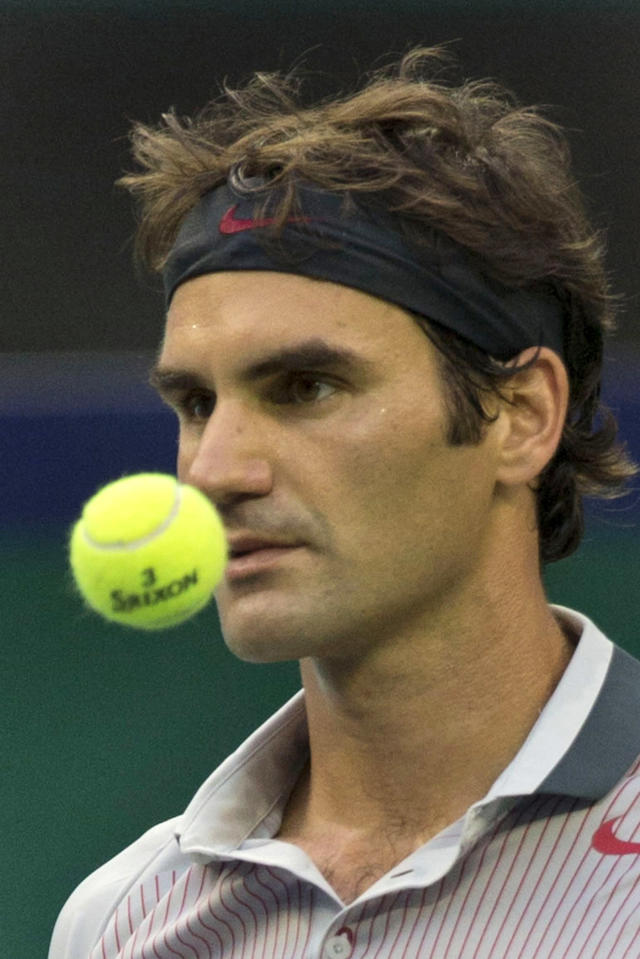 Switzerland's Roger Federer tosses a ball as he pauses during a match against France's Gael Monfils at the Shanghai Masters tennis tournament at the Qizhong Forest Sports City Tennis Center in Shanghai, China, Thursday, Oct. 10, 2013. Monfils won 6-4, 6-7, 6-3. (AP Photo/Ng Han Guan)