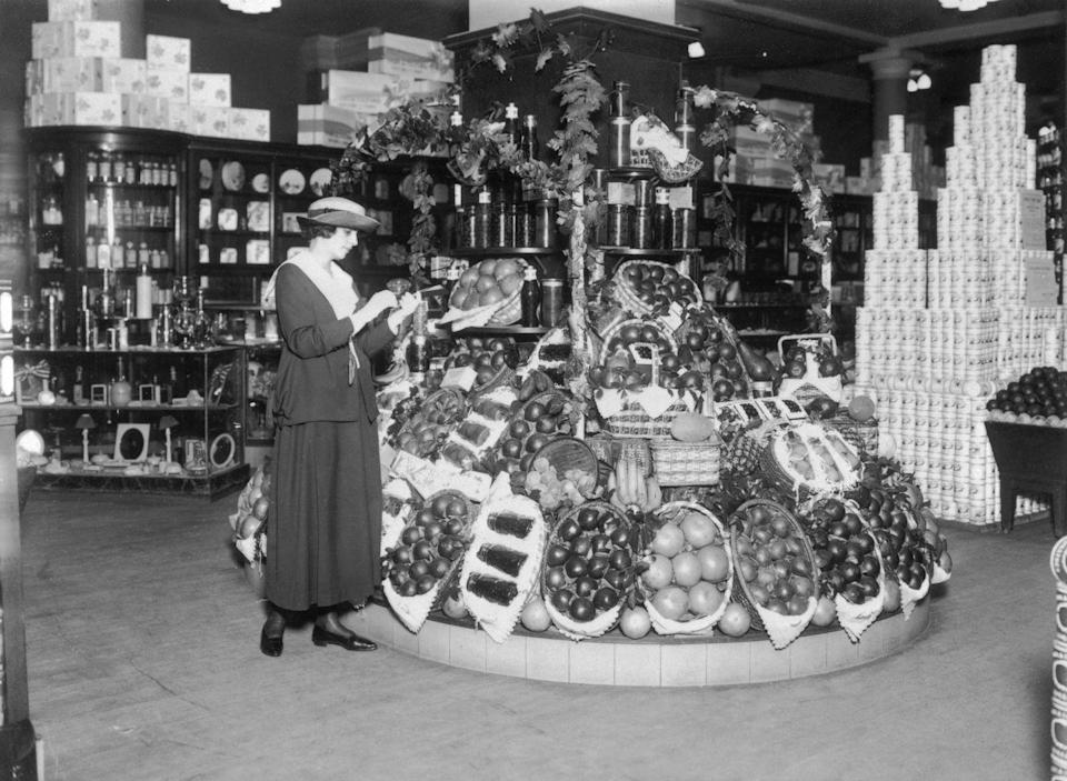 <p>Walmart wasn't the first store to sell groceries and home décor all in one place. As seen in this photo, a woman inspects the fruit and vegetables on display at a general store. However, a closer inspection reveals the picture frames and candle sticks of the home décor section directly behind her.</p>