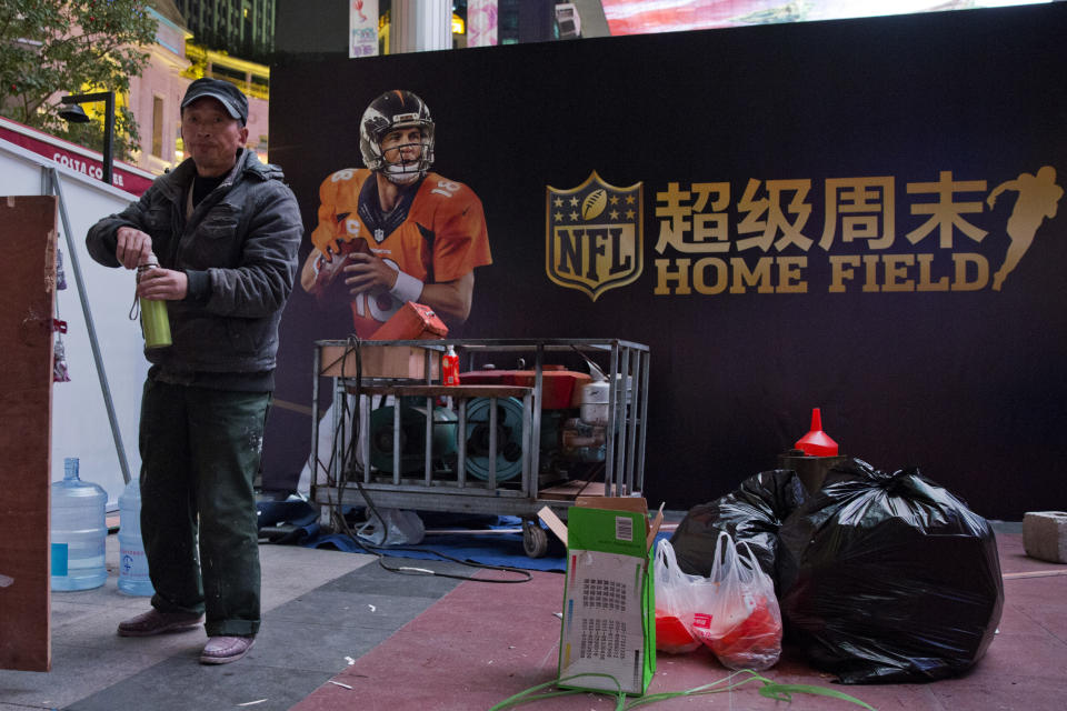 A worker turns the cap of his thermos near a billboard promoting a National Football League event in Beijing, China, Thursday, Oct. 22, 2015. The NFL has been aggressively promoting football in China hoping to take advantage of rising income and growing taste for exotic foreign sports. (AP Photo/Ng Han Guan)