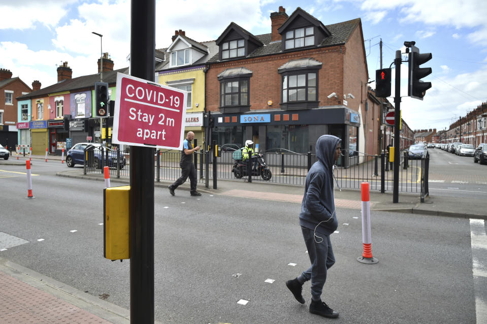 People walk in Melton Road also known as the Golden Mile in Leicester, England, Tuesday June 30, 2020. The British government has reimposed lockdown restrictions in the English city of Leicester after a spike in coronavirus infections, including the closure of shops that don't sell essential goods and schools. (AP Photo/Rui Vieira)