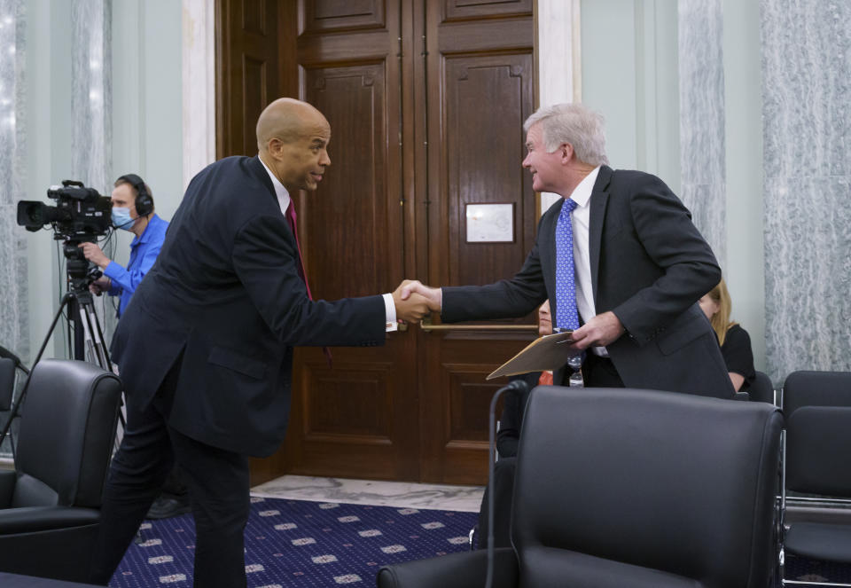 Sen. Cory Booker, D-N.J., left, greets NCAA President Mark Emmert, as the Senate Commerce, Science, and Transportation Committee holds a hearing on student athlete compensation and federal legislative proposals to enable athletes participating in collegiate sports to monetize their name, image, and likeness, at the Capitol in Washington, Wednesday, June 9, 2021. (AP Photo/J. Scott Applewhite)