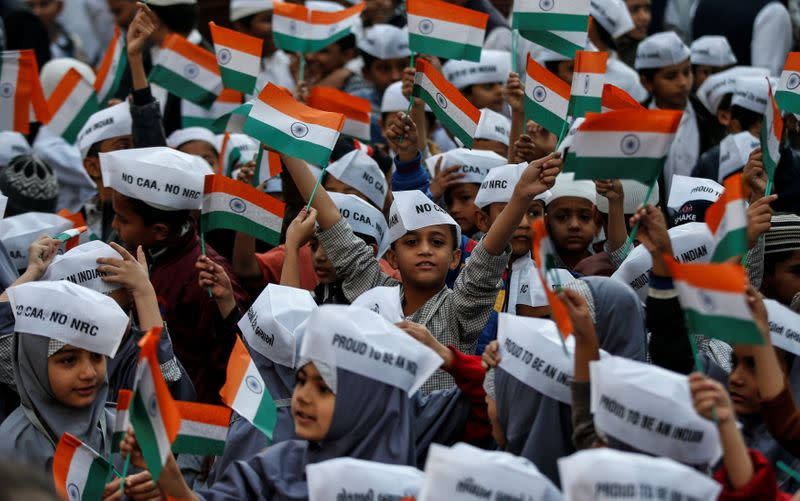 School children wearing caps with writings against a new citizenship law attend Republic Day celebrations in Ahmedabad