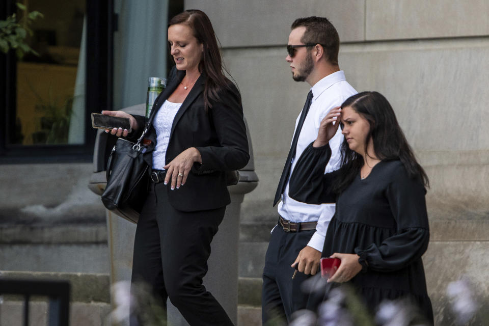 Trevor Gray, 18, center, and defense attorney Jessica Mainprize-Hajek, left, exit the Genesee County Circuit Court, Tuesday, Aug. 3, 2021 in Flint, Mich., after Gray, MarkSekelsky, 19, and Mikadyn Payne, 19, were sentenced to probation for their part in a 2017 rock-throwing incident that killed a motorist on Interstate 75 after spending more than three years in custody while their case was stuck in court. (Isaac Ritchey/The Flint Journal via AP)