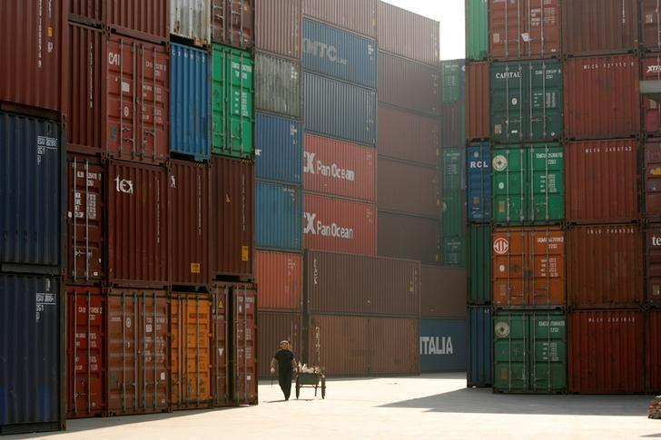 FILE PHOTO - Woman walks past containers at port in Shanghai