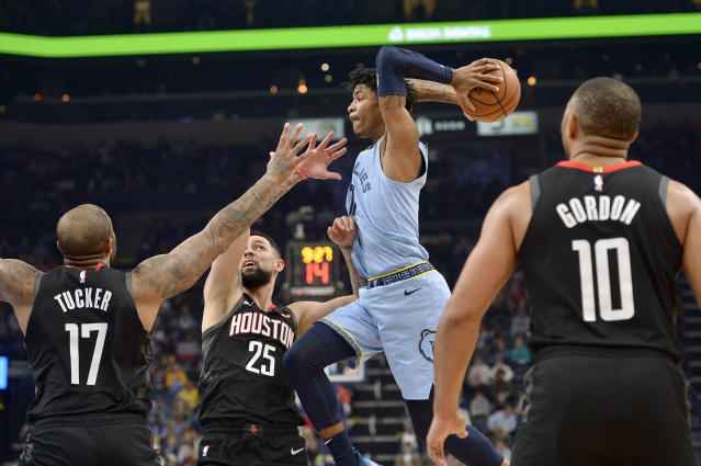 Memphis Grizzlies guard Ja Morant looks to pass the ball over Houston Rockets forward PJ Tucker (17) and guard Austin Rivers (25) during the second half of an NBA basketball game Tuesday, Jan. 14, 2020, in Memphis, Tenn. (AP Photo/Brandon Dill)