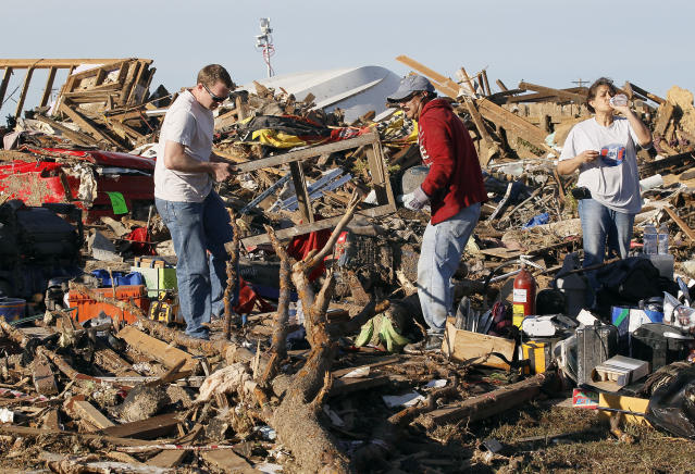 People salvage belongings from their tornado-ravaged homes in Moore, Oklahoma May 21, 2013. Rescuers went building to building in search of victims and thousands of survivors were homeless on Tuesday after a massive tornado tore through the Oklahoma City suburb of Moore, wiping out whole blocks of homes and killing at least 24 people. REUTERS/Rick Wilking (UNITED STATES - Tags: DISASTER ENVIRONMENT) - RTXZVQS