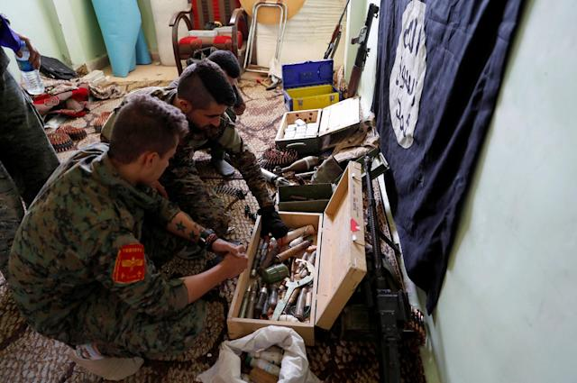 <p>Fighters of Syrian Democratic Forces inspect weapons and munitions recovered at the former positions of the Islamic State militants inside a building at the frontline in Raqqa, Syria, Oct. 7, 2017. (Photo: Erik De Castro/Reuters) </p>
