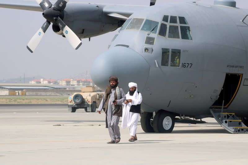 FILE PHOTO: Taliban walk in front of a military airplane a day after the U.S. troops withdrawal from Hamid Karzai International Airport in Kabul